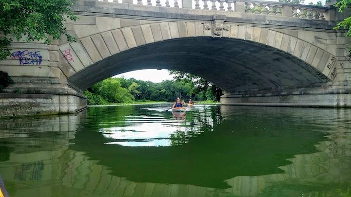 kayaking under a bridge lake of the isles